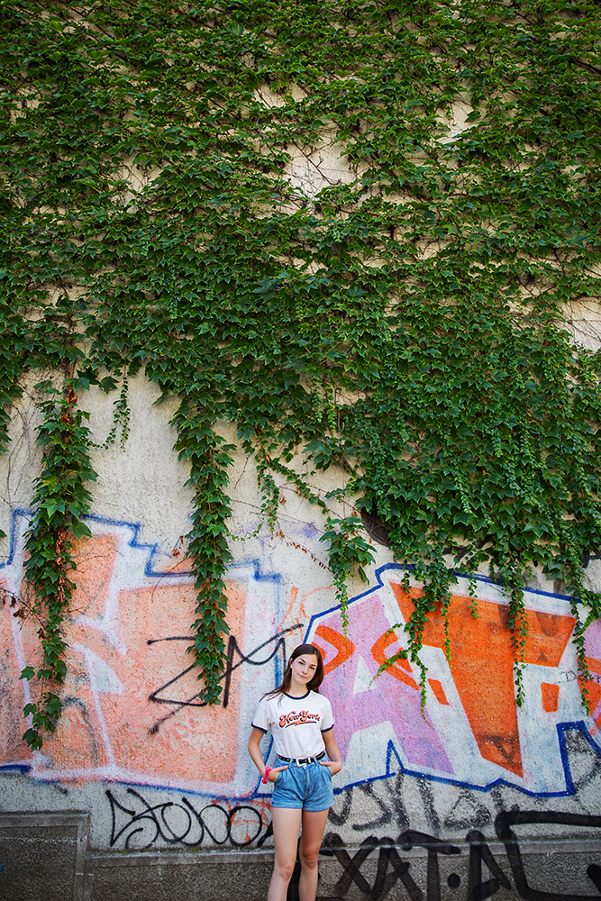 Teen girl in front of a vine covered wall of graffiti in Slovenia