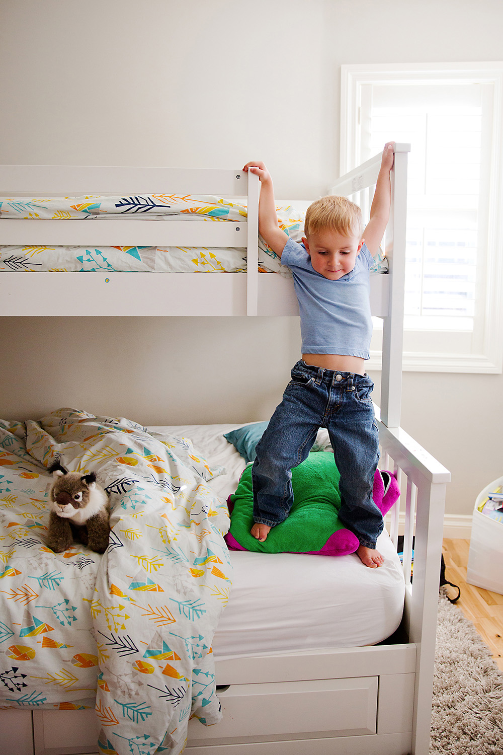 Boy awkwardly climbing down from the top bunk by Dana Pugh