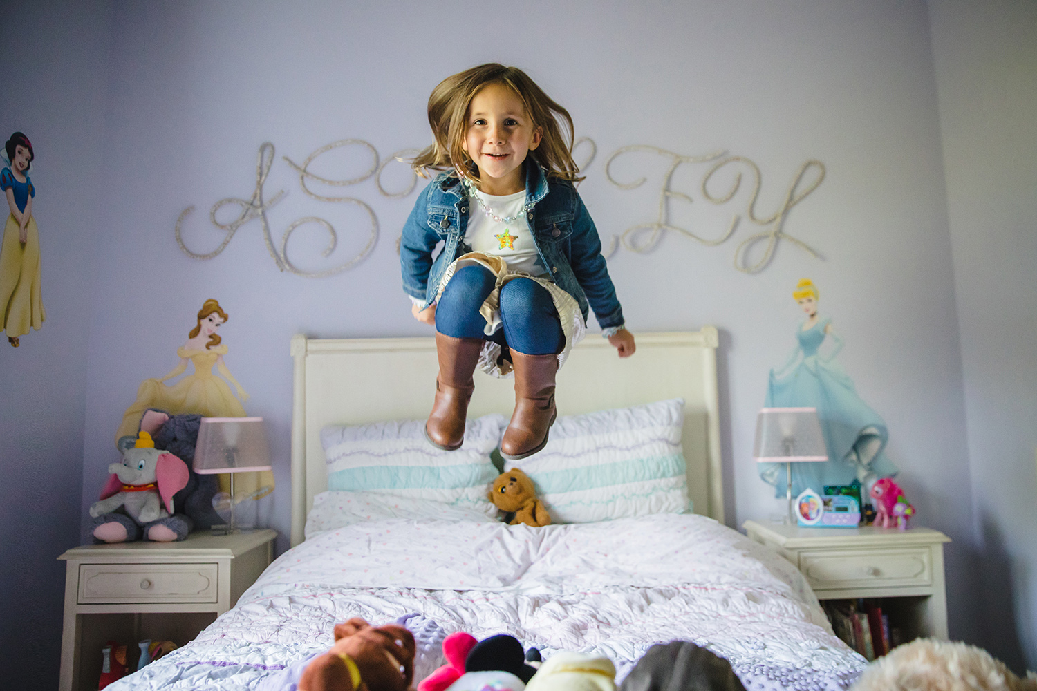 girl jumping on the bed in her bedroom
