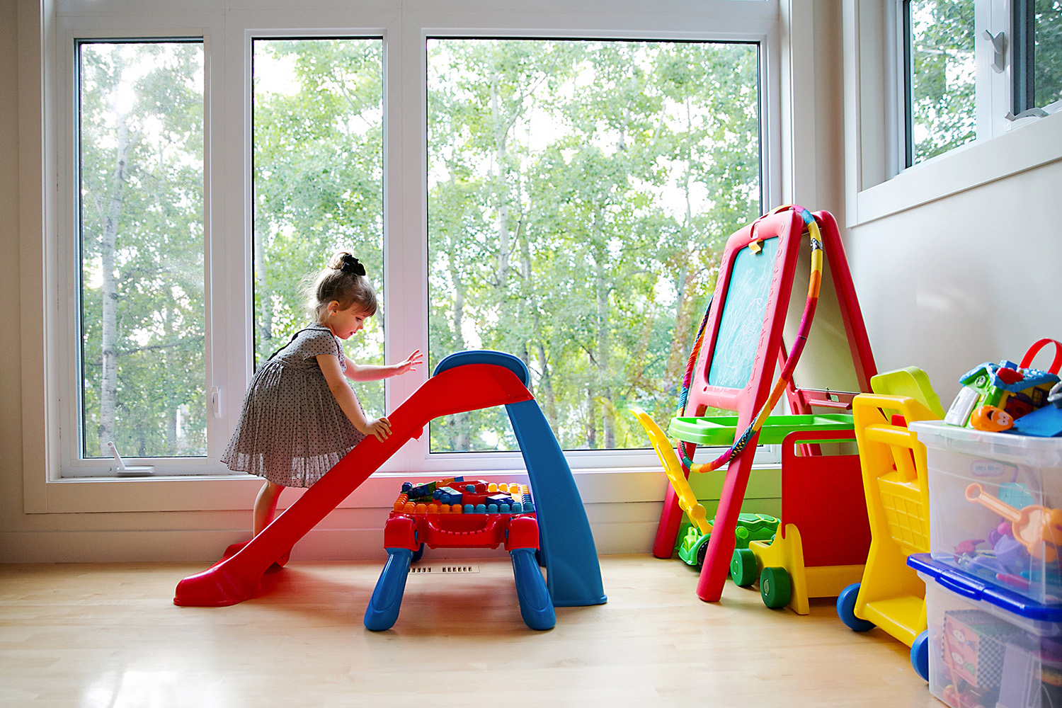 Toddler playing in her colorful playroom by Dana Pugh
