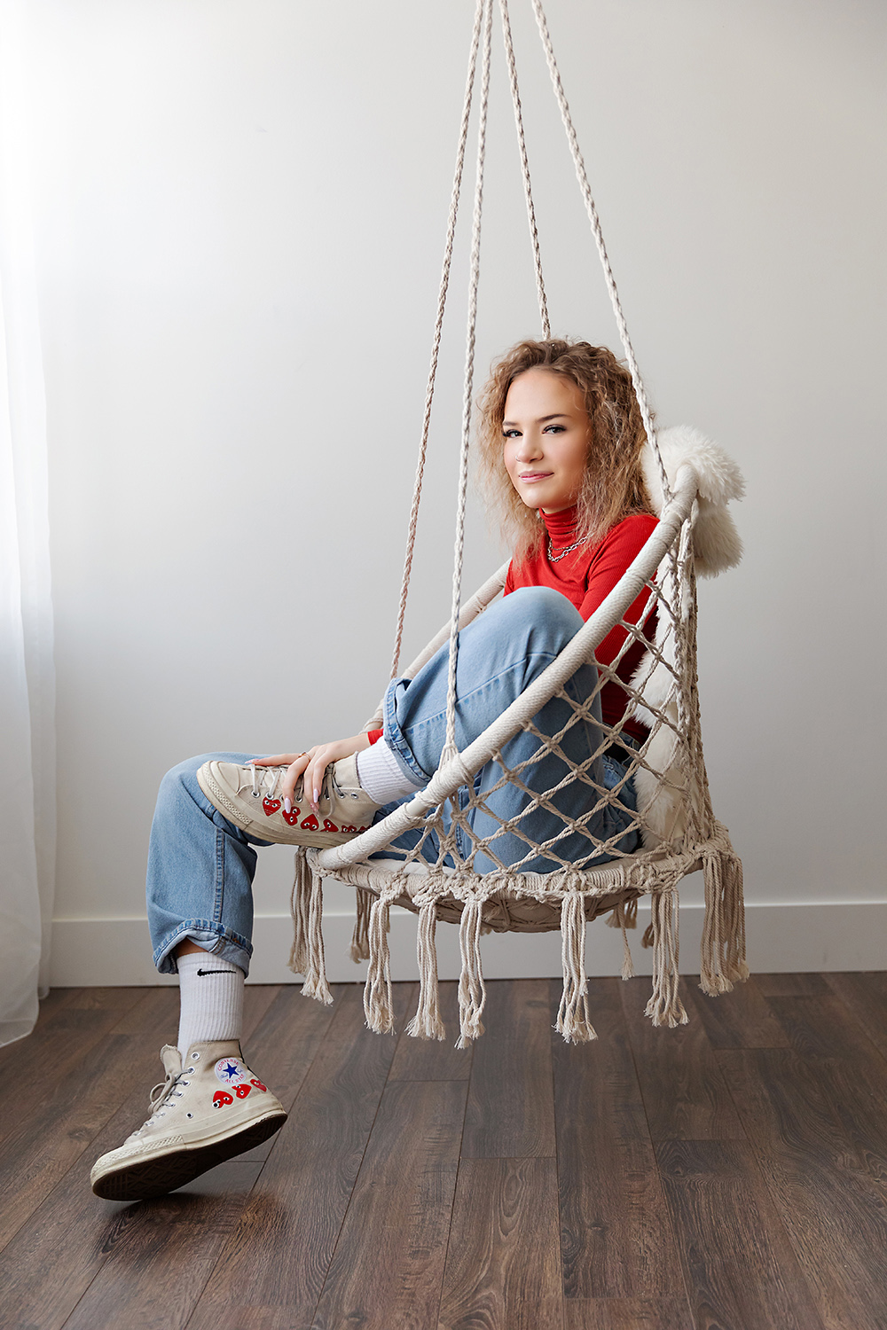 Converse wearing teenager on a crochet swing