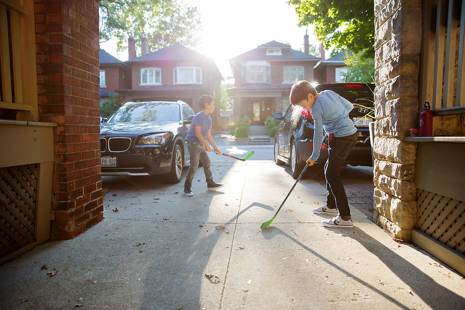 Brothers playing hockey in the front driveway in Toronto