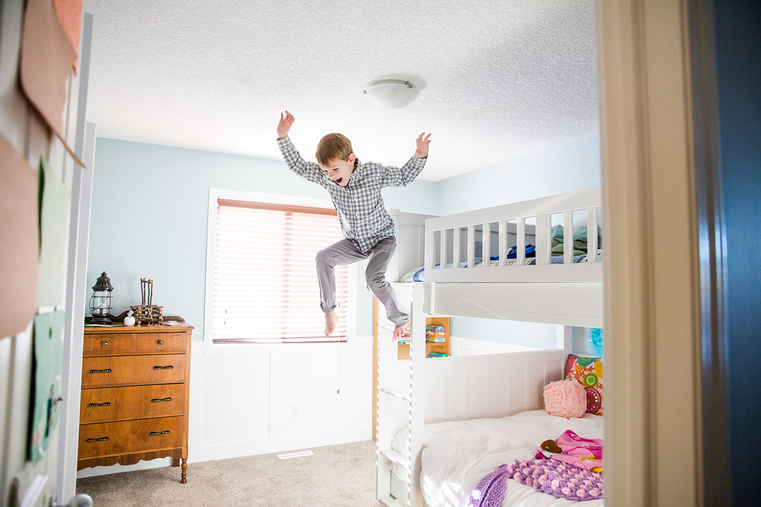 Boy jumping off of his bunk bed by lifestyle photographer, Dana Pugh