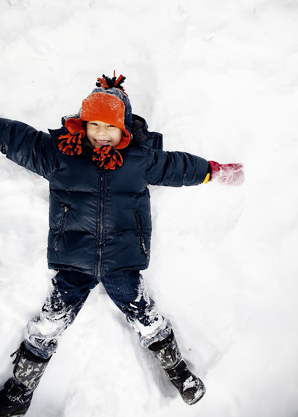 Lifestyle portrait of a boy making a snow angel