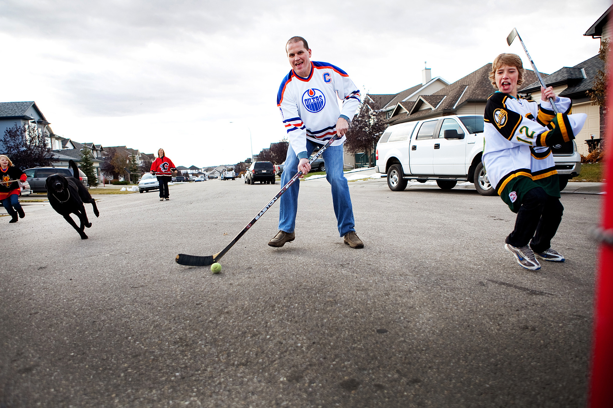 Family playing street hockey together