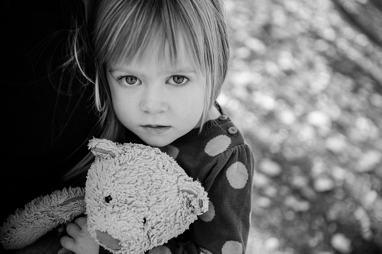 Small child hugging her teddy bear