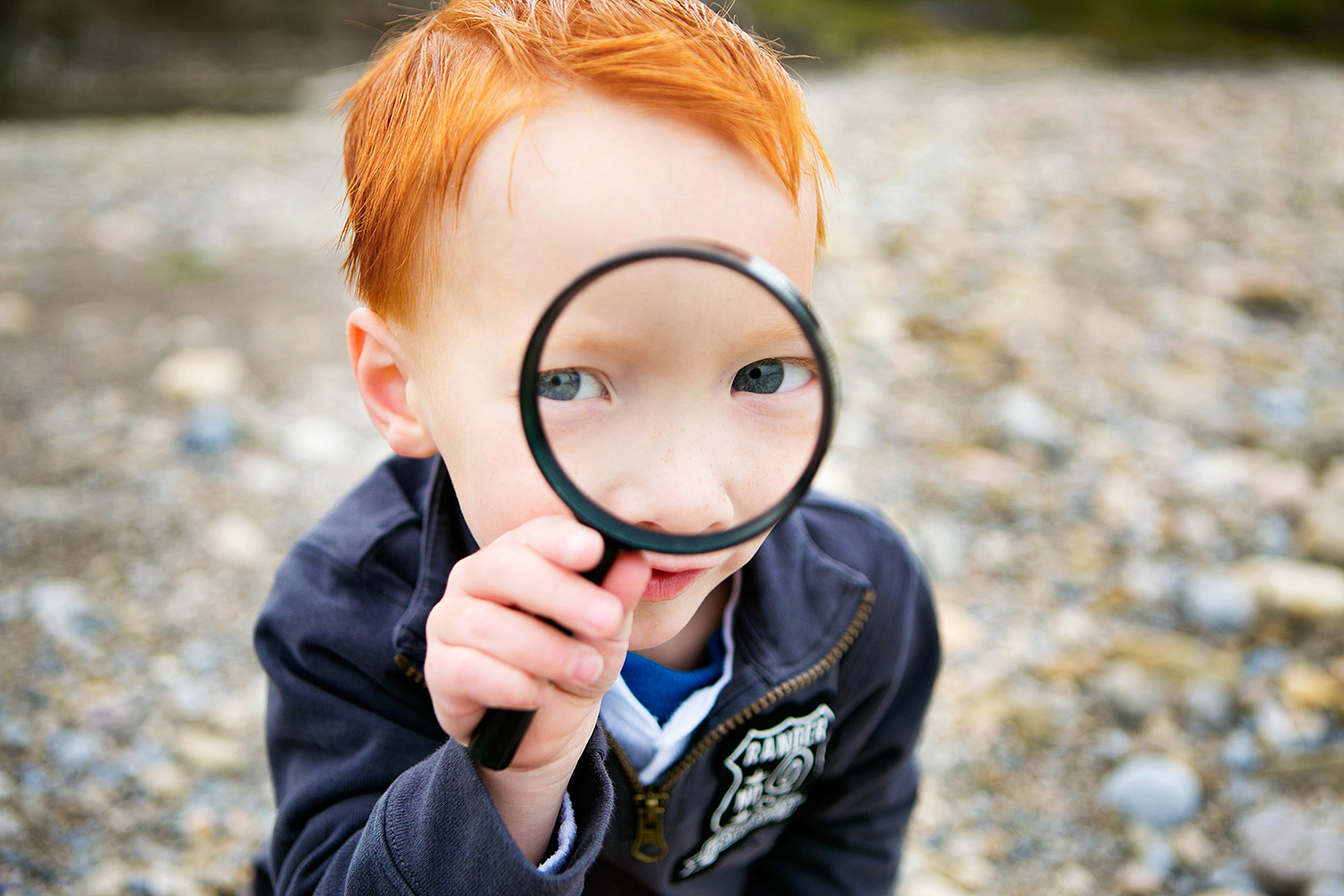 Red head boy looking through a magnifying glass