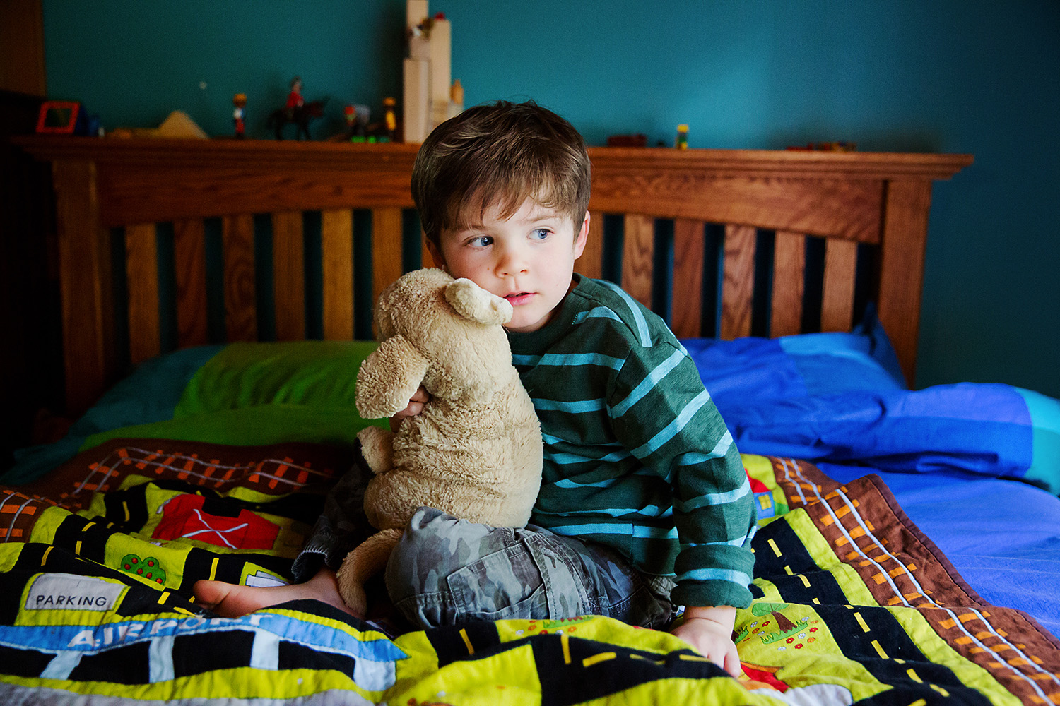 Child with his teddy bear in his bedroom
