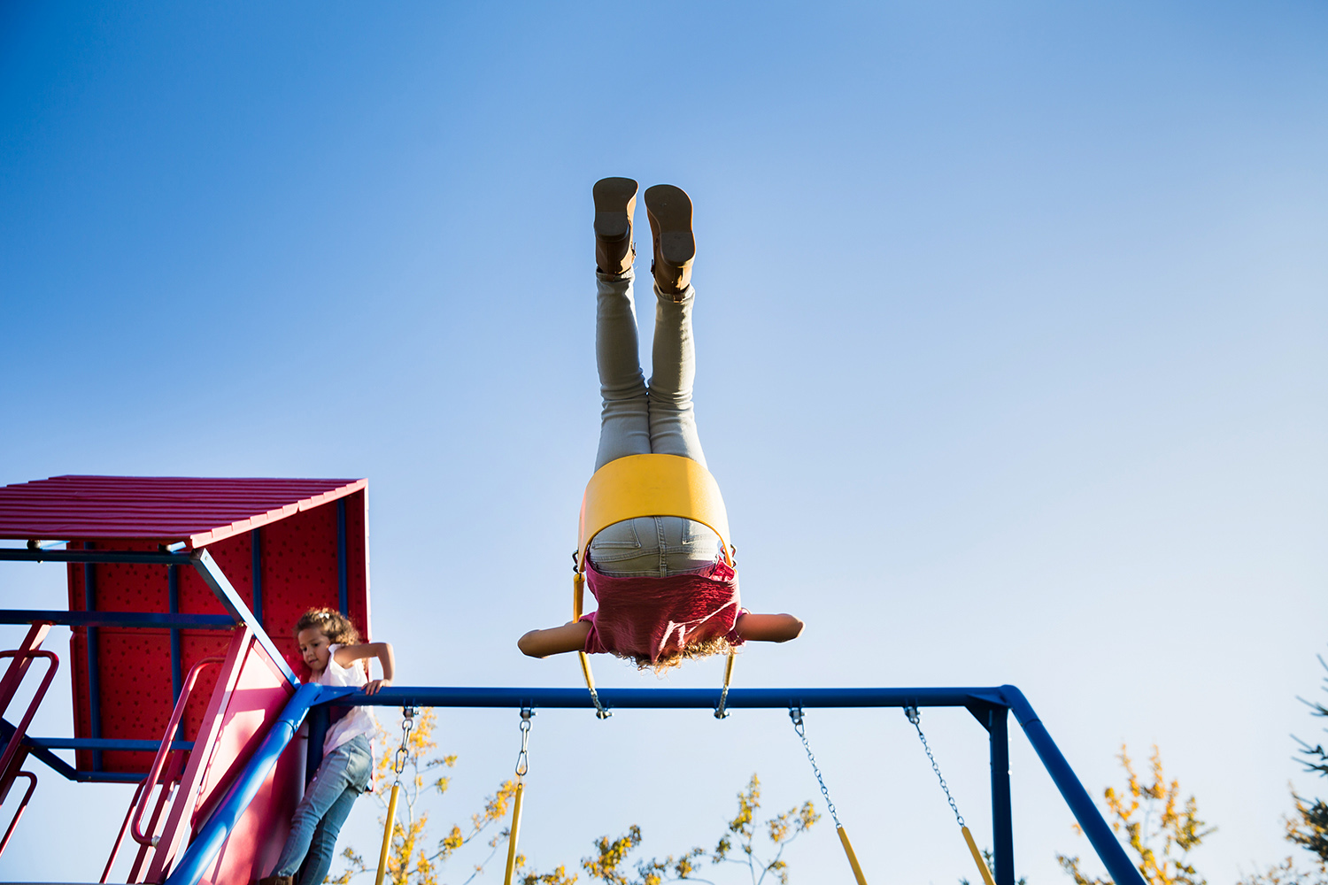 children swinging on their backyard play structure