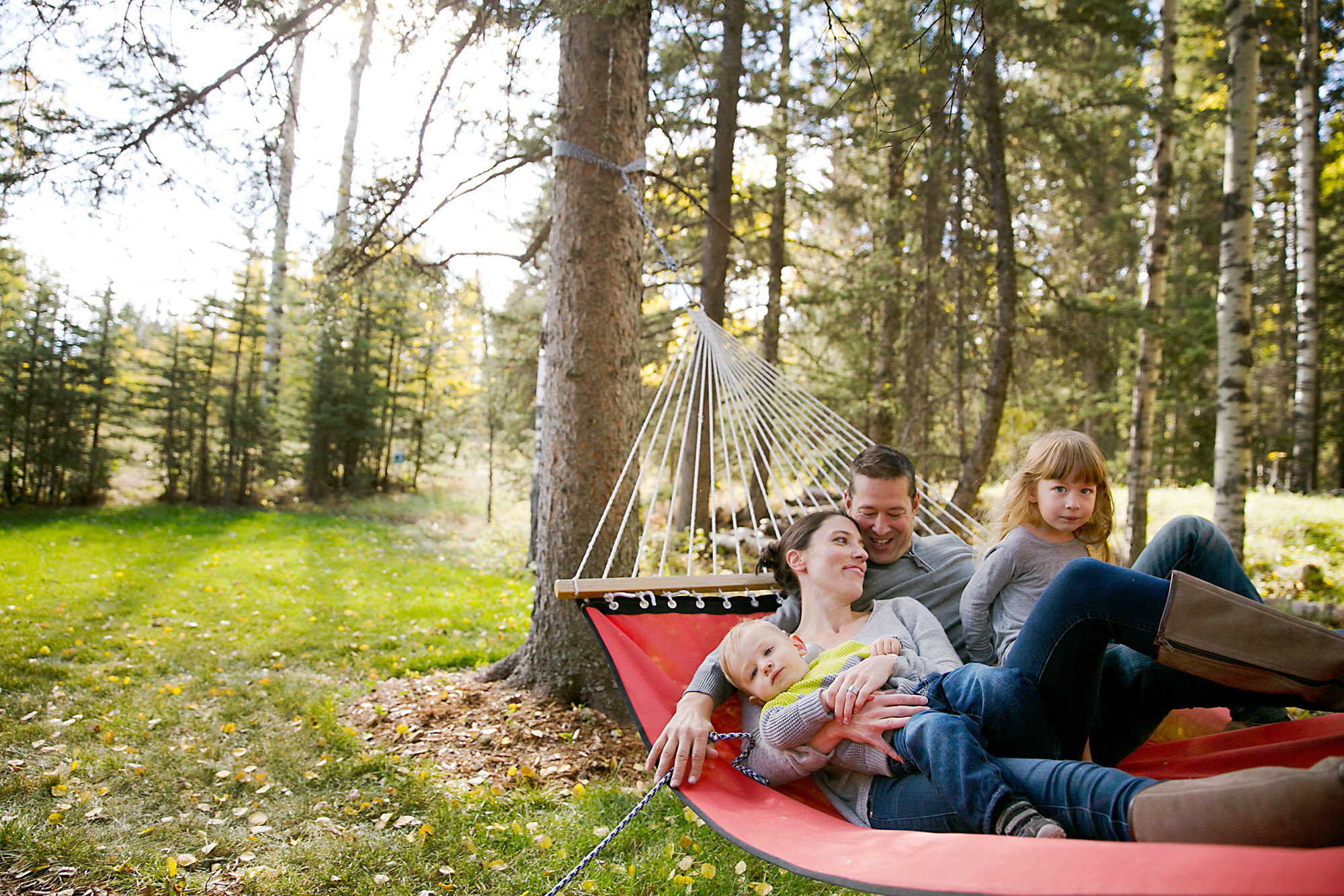Family relaxing on their backyard hammock