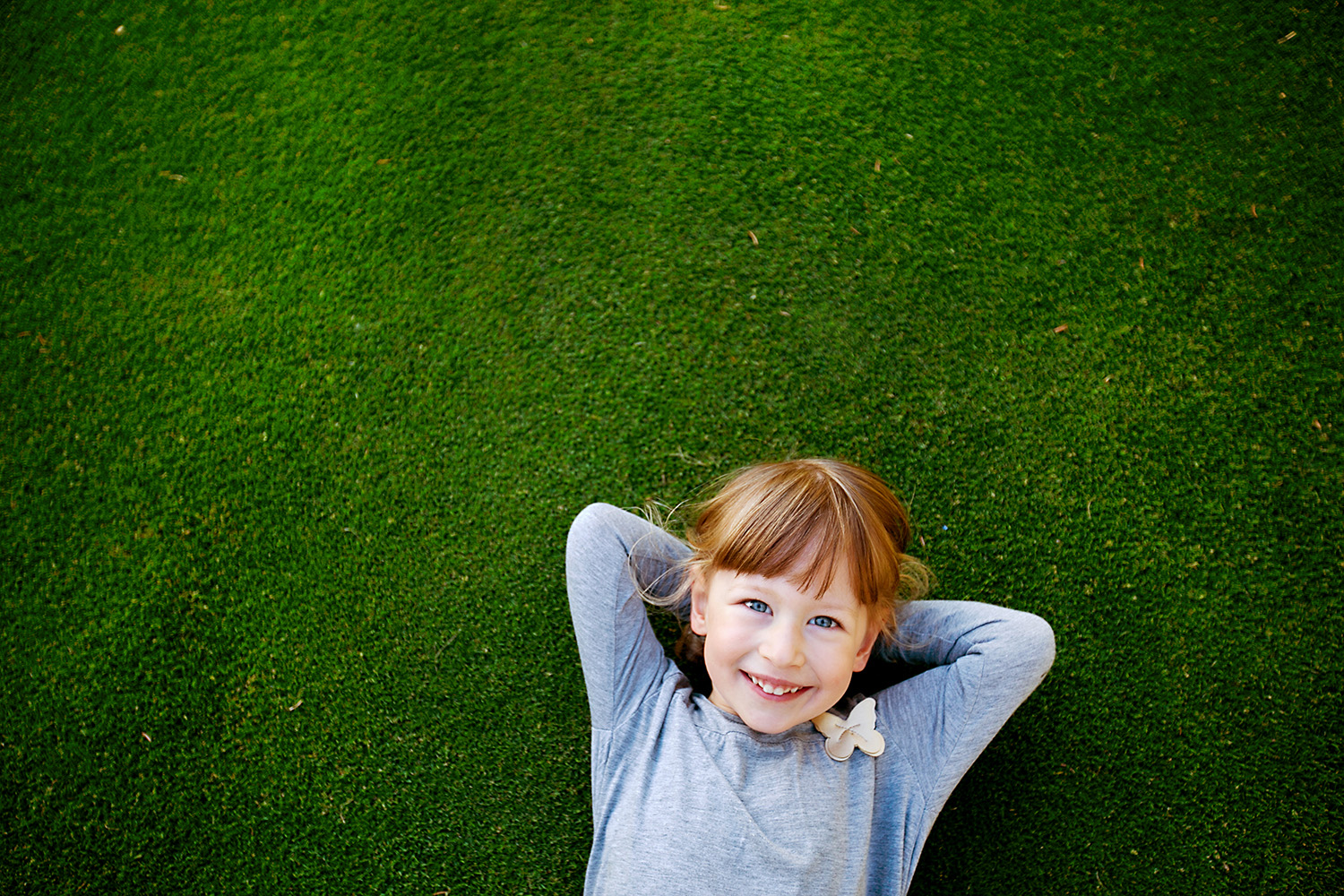 Daydreaming child laying in the grass