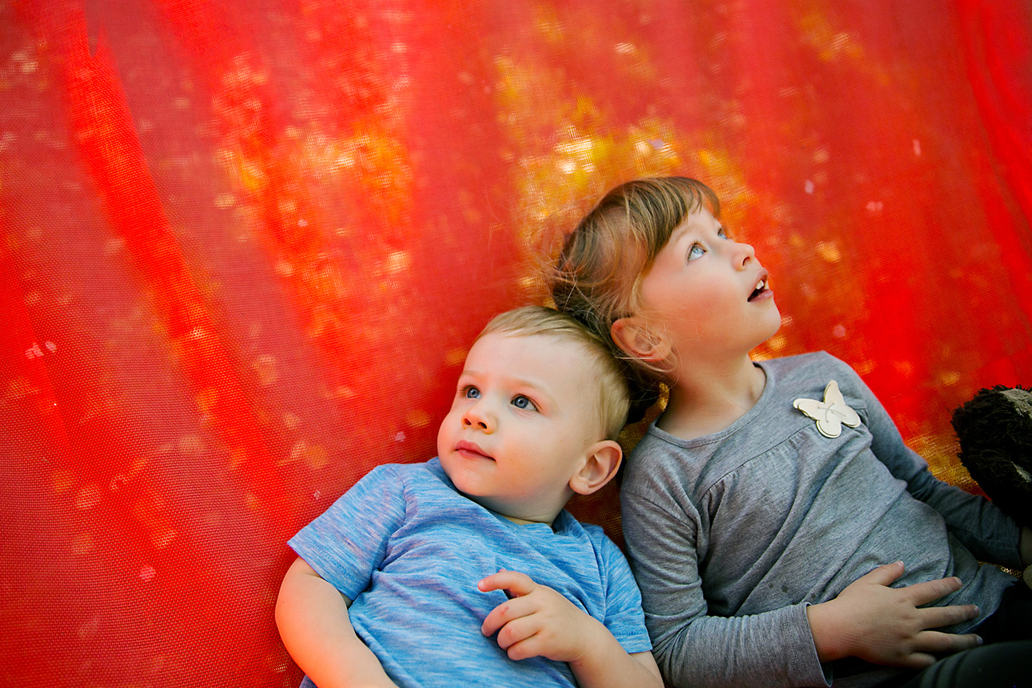 Siblings daydreaming on a hammock by Dana Pugh