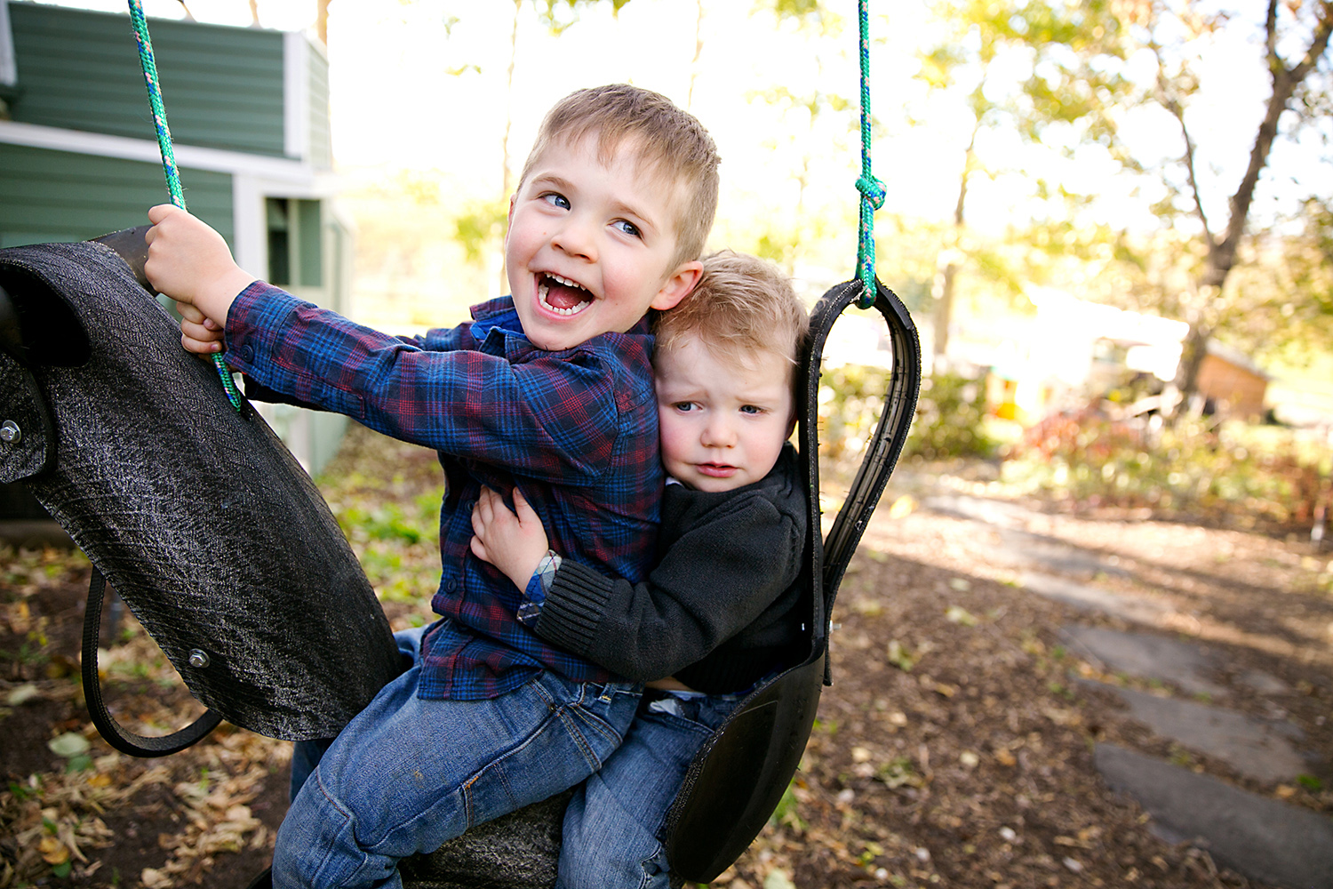 Brothers on a tire swing by Dana Pugh
