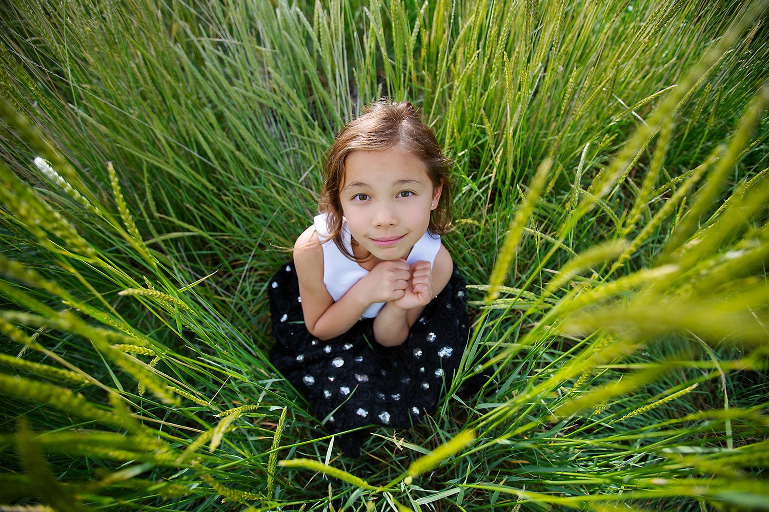Girl hiding in the grass by Canadian Commercial photographer
