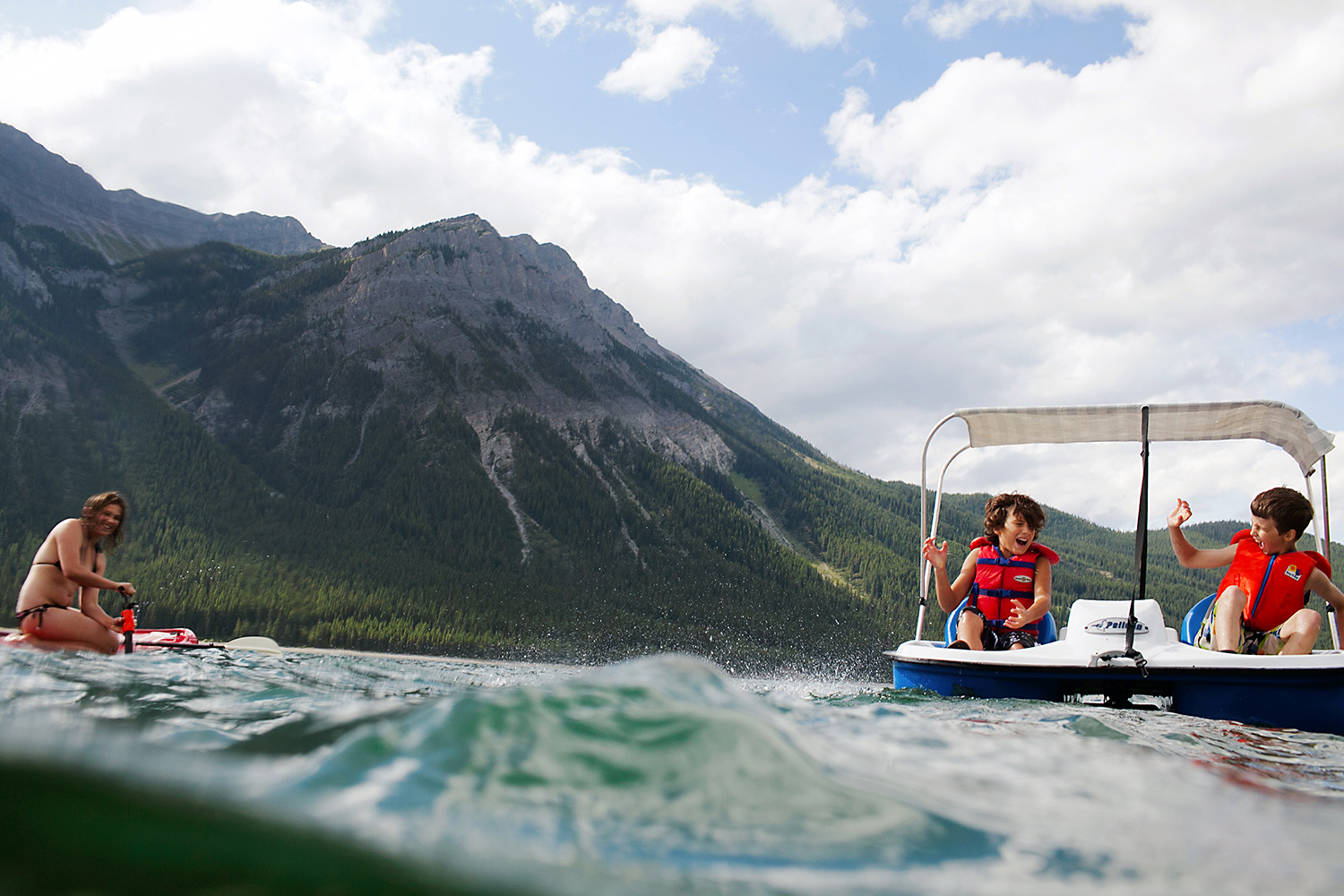 Children playing in a paddle boat in Kananaskis, Alberta