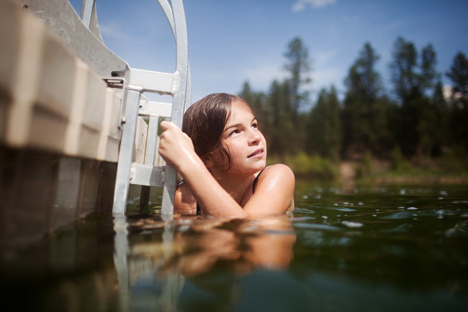 girl swimming to a floating deck in British Columbia