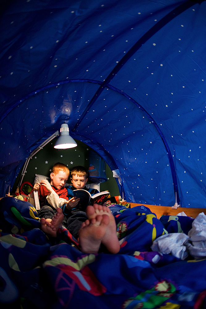 Brothers reading books together in a tent