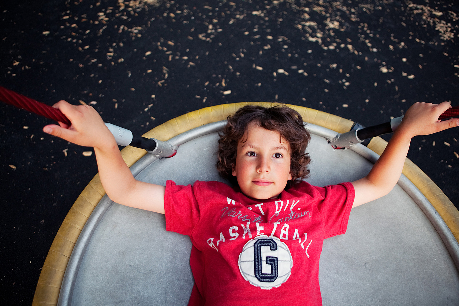 Boy with curly hair on a playground saucer