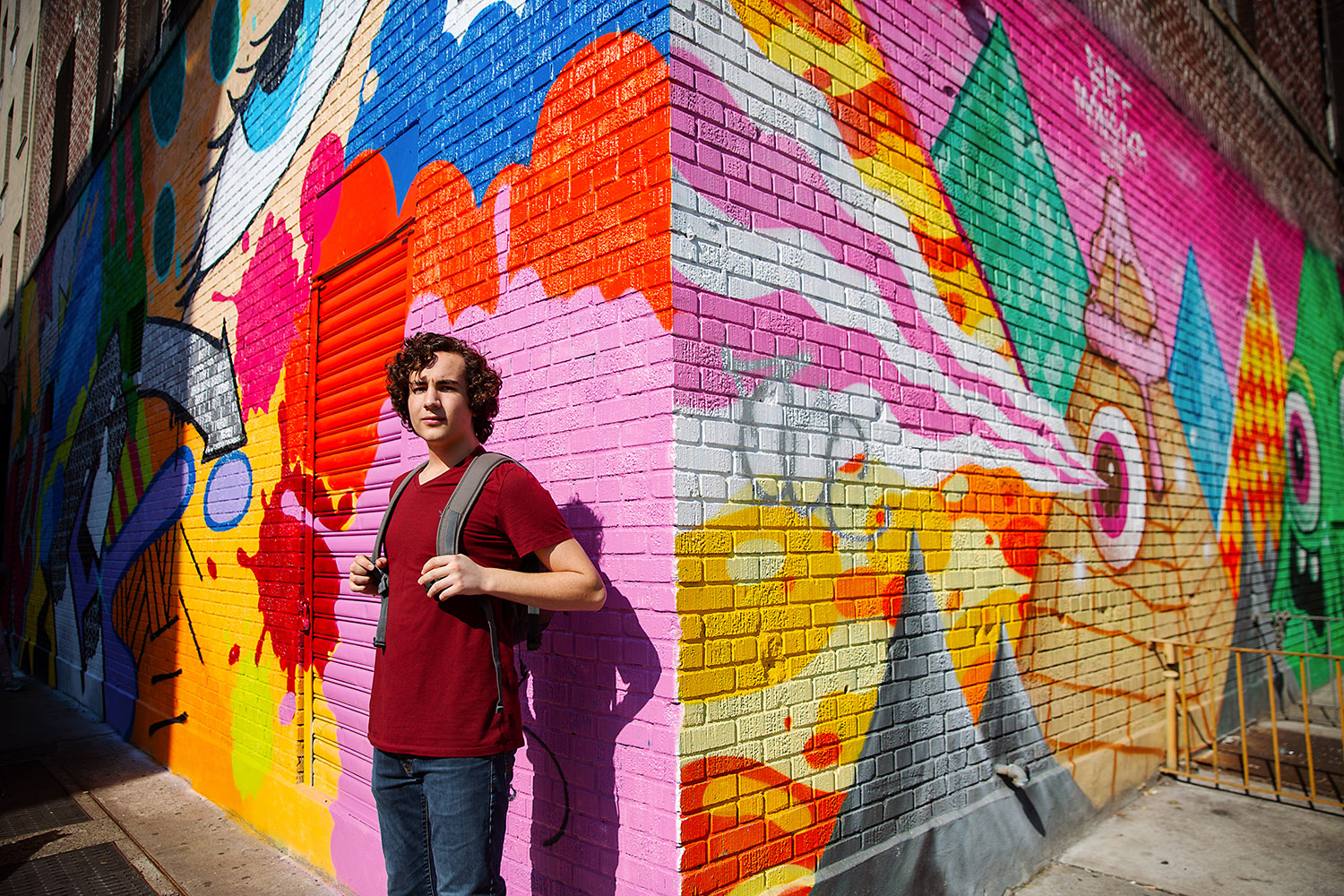 Teenaged boy in front of a graffiti mural in NYC