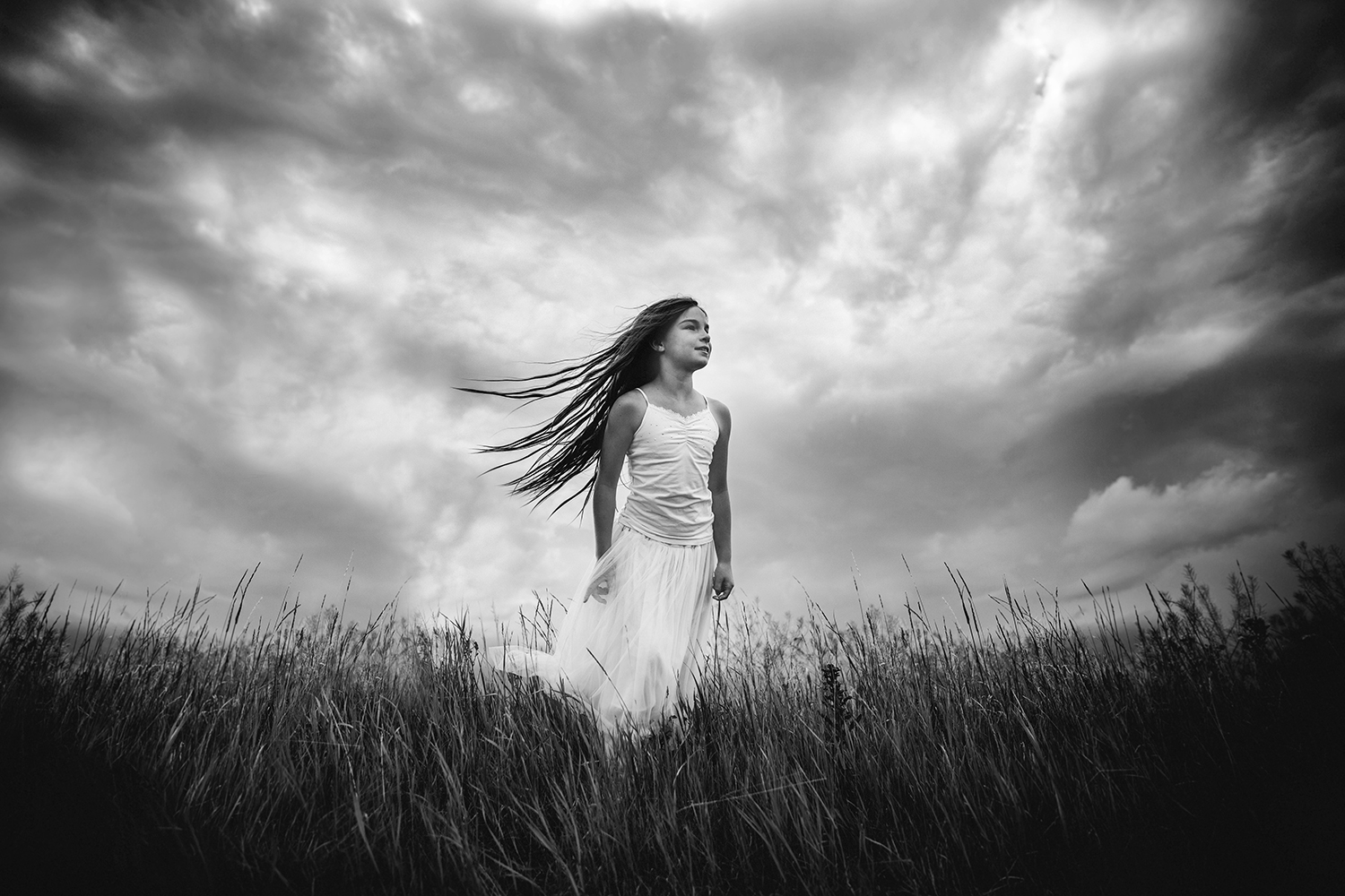 Lifestyle portrait of a girl against a stormy sky