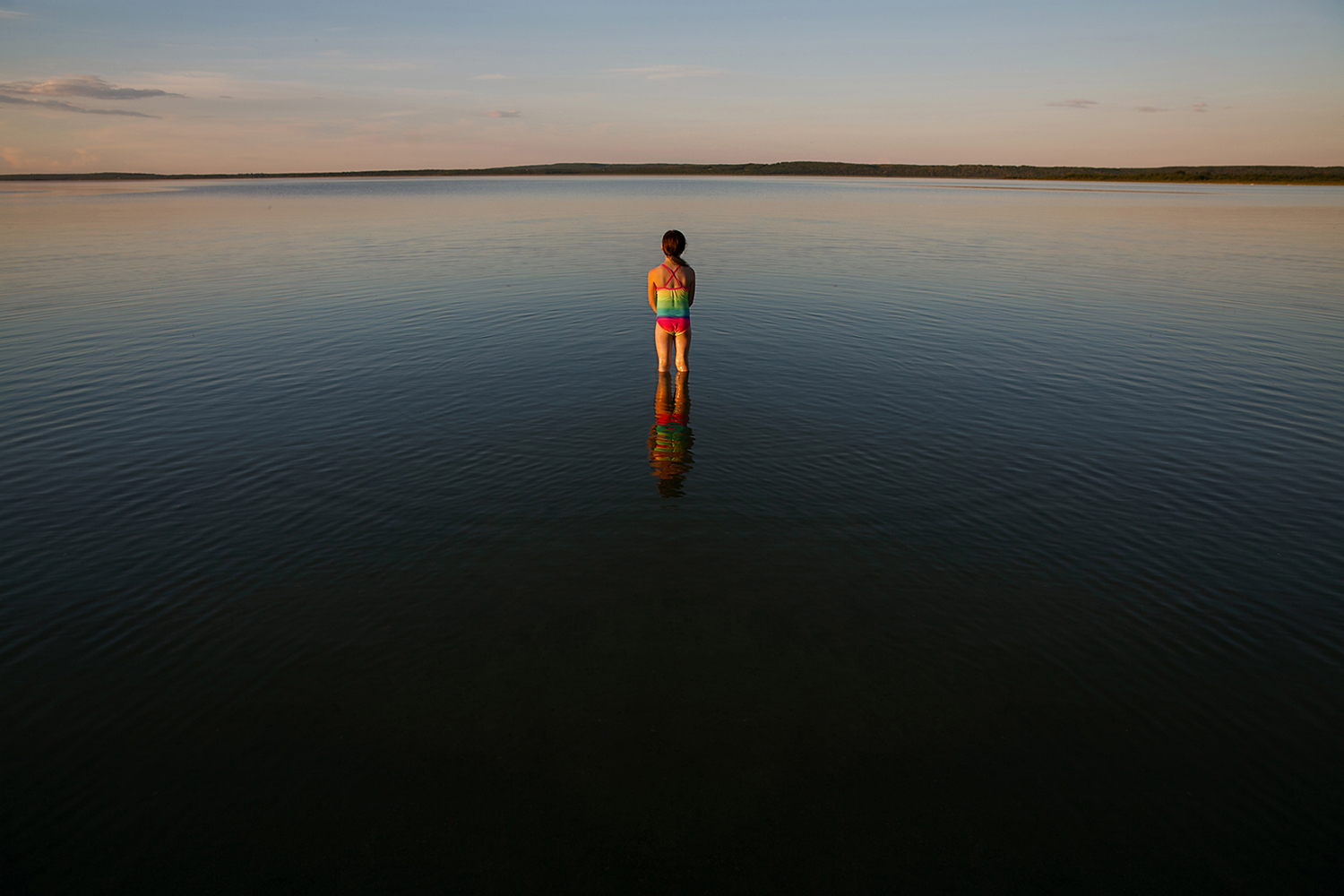 Girl standing out in a calm lake as the sun sets