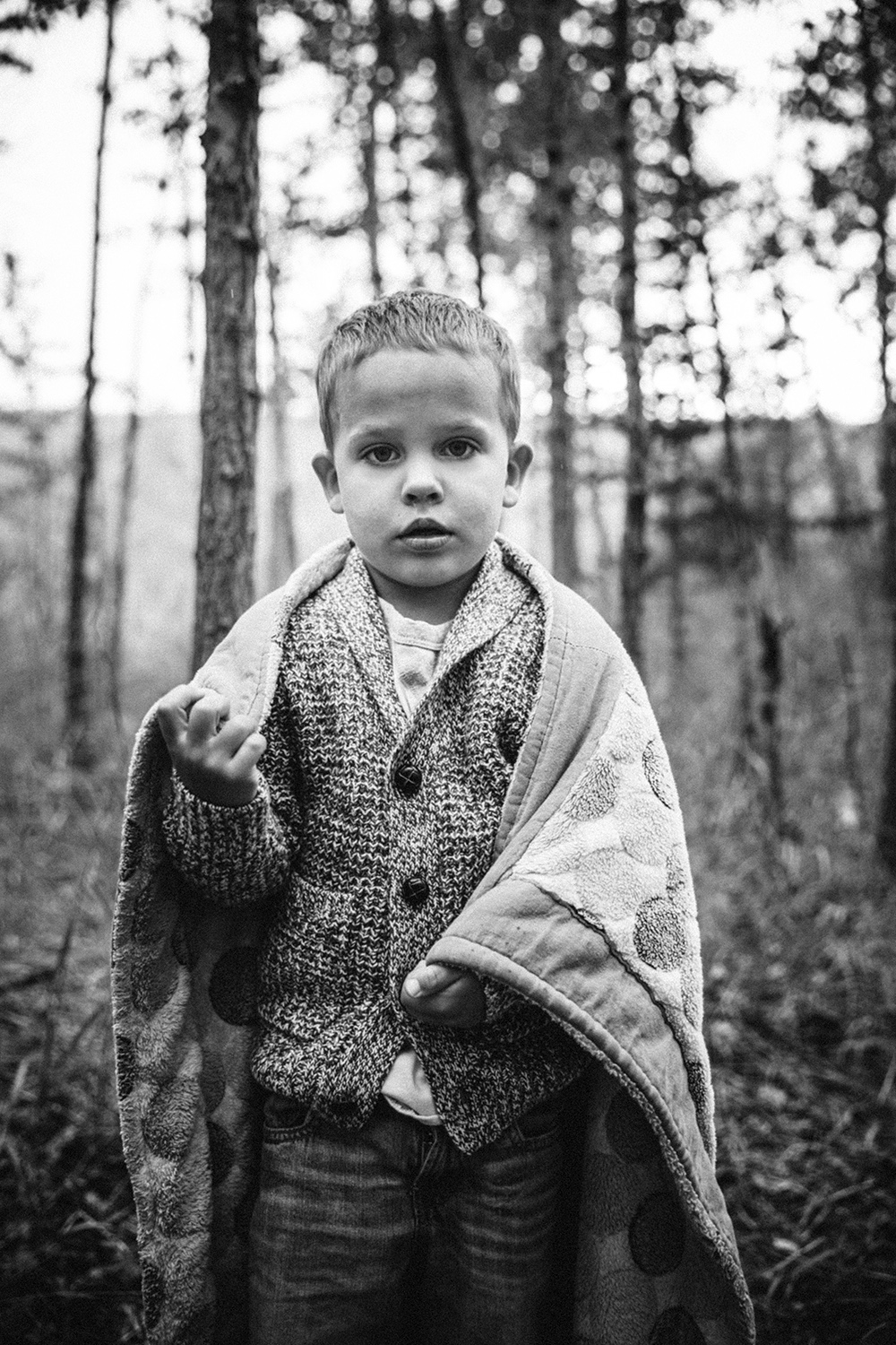 Editorial image of a boy wrapped in his favourite blanket