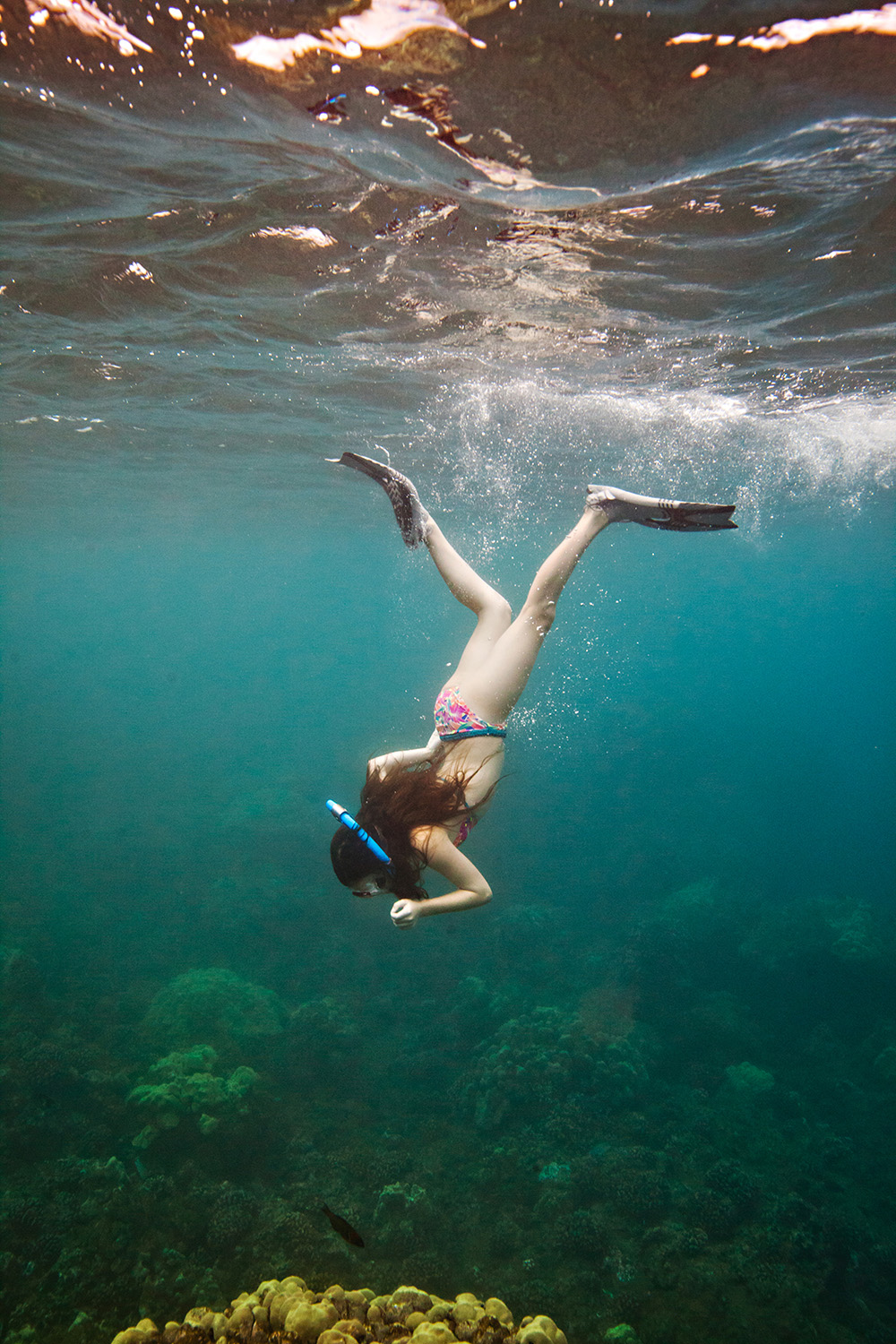 Child snorkelling underwater in Hawaii