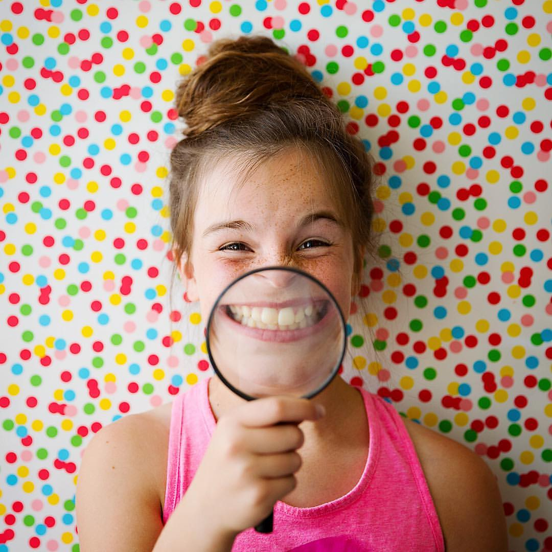 Portrait of a girl with a magnified glass