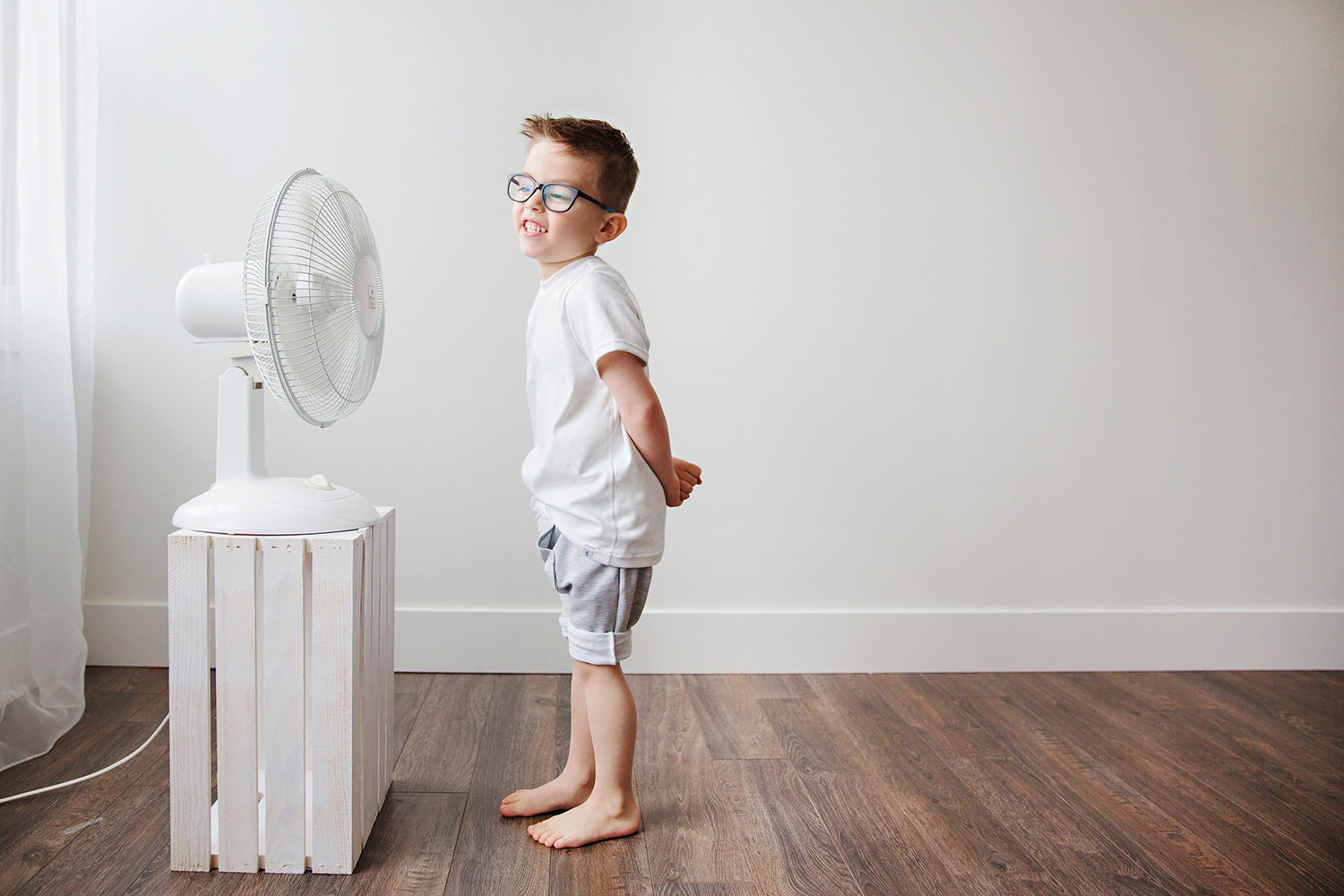 Studio fashion portrait of a boy in front of a fan